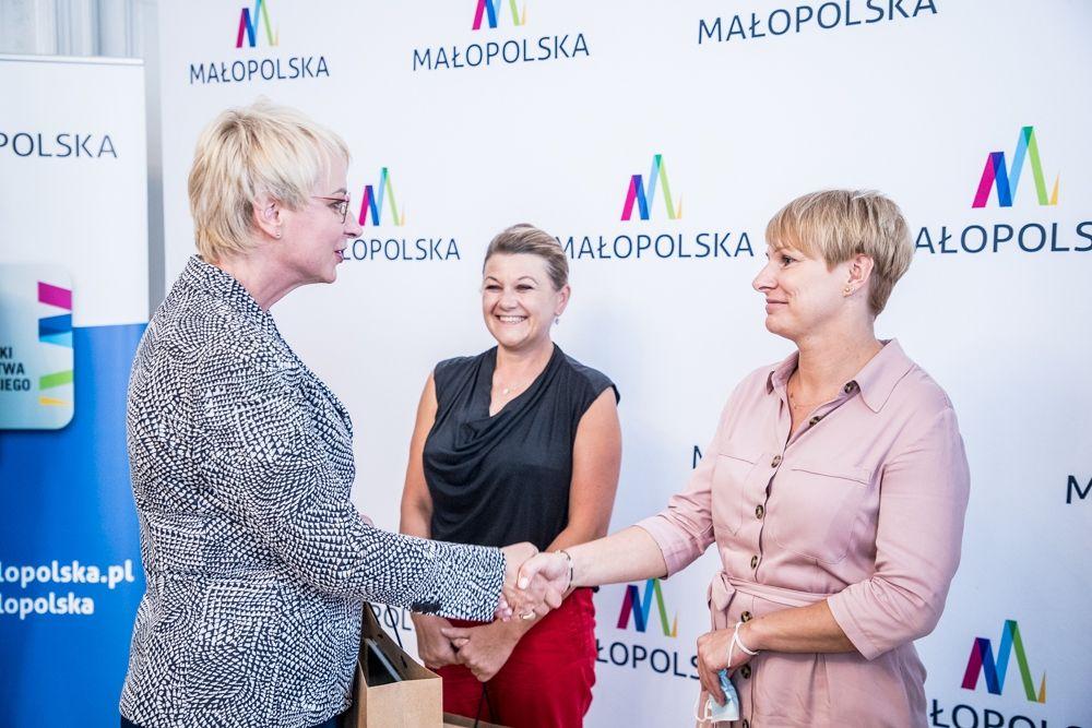 Na zdjęciu widoczne są 3 osoby. Kobieta przekazuje gratulacje z okazji wyłonienia laureatów 5. edycji Budżetu Obywatelskiego.