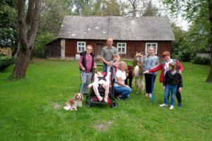 Grupa opiekunów i wychowanków pozuje z alpakami