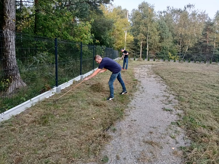 """Na zdjęciu widoczne są 2 osoby. Uczestnicy projektu """"Droga do samodzielności"""" grabią trawę."""