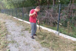 """Na zdjęciu widoczna jest 1 osoba. Uczestnik projektu """"Droga do samodzielności"""" grabi trawę."""