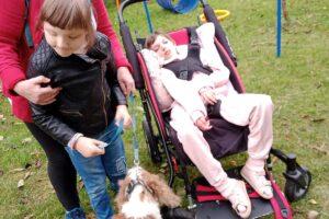 Opiekun trzyma wychowankę, obok stoi wózek z wychowankiem. Obok stoi pies, który zwrócony jest w grupę osób.