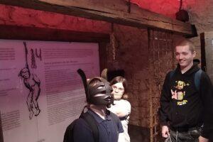 Na zdjęciu wychowanek stoi w zabytkowym hełmie podczas wycieczki do Podziemnego Olkusza. Inny wychowanek się przygląda.