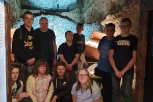 Na zdjęciu widać grupę wychowanków - 10 osób, które pozują w jednej z sal Podziemnego Olkusza.