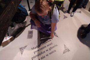 Na zdjęciu widać wychoankę, która czyta napisz podczas wycieczki w Podziemnym Olkuszu.