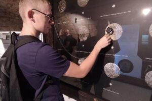 Na zdjęciu widać wychowanka, który podczas zwiedzana dotyka specjalnie do tego przygotowanej ekspozycji.