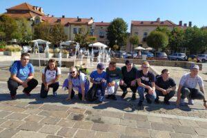 Na zdjęciu widać grupę wychowanków 9 osób, które kucają na olkuskim rynku.