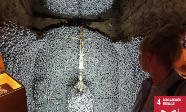 Na zdjęciu widać osobę, która patrzy na srebrną grotę z krzyżem.