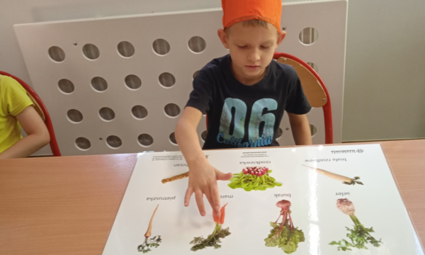 Na zdjęciu wychowanek pokazuje na planszy marchewkę