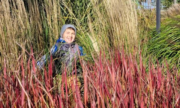 Na zdjęciu widzimy wychowanka, który stoi pośród dużych traw
